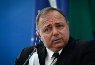 Ex-ministro da Saúde, Eduardo Pazuello, tira máscara em frente a um microfone.